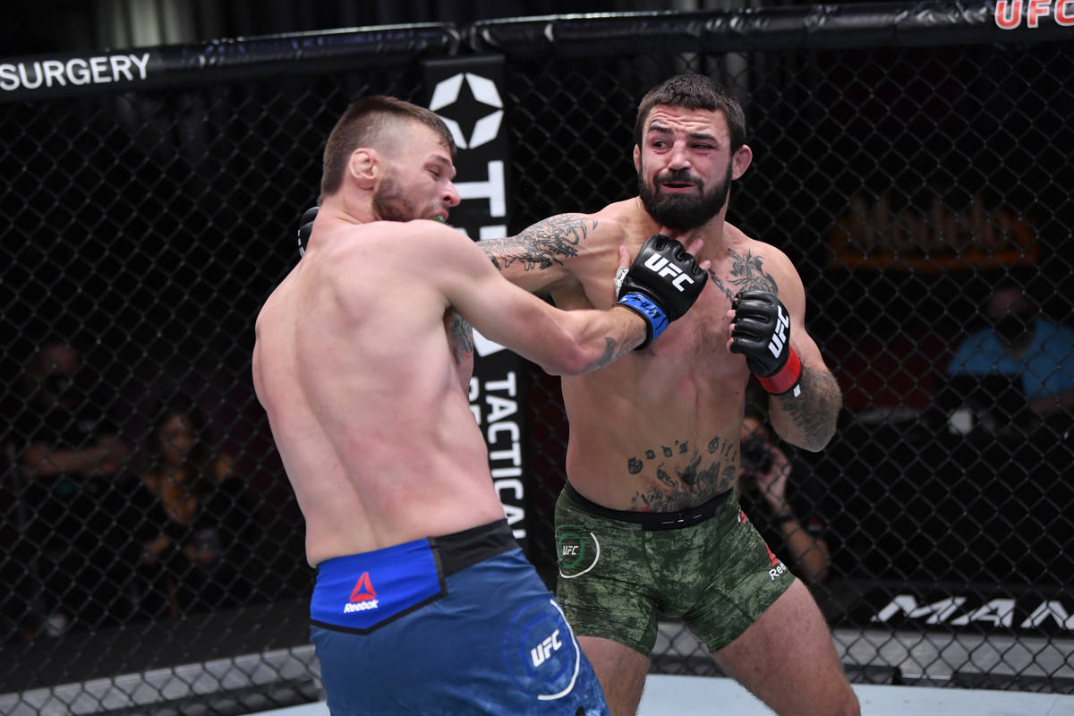 LAS VEGAS, NEVADA - NOVEMBER 21: (R-L) Mike Perry punches Tim Means in their welterweight bout ...