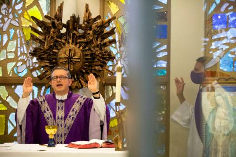 Msgr. Gregory Gordon, left, gives a virtual Mass at the The Roman Catholic Diocese of Las Vegas ...