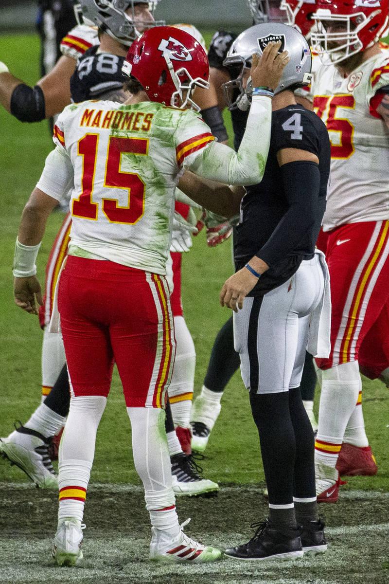 Kansas City Chiefs quarterback Patrick Mahomes (15) pats Las Vegas Raiders quarterback Derek Ca ...