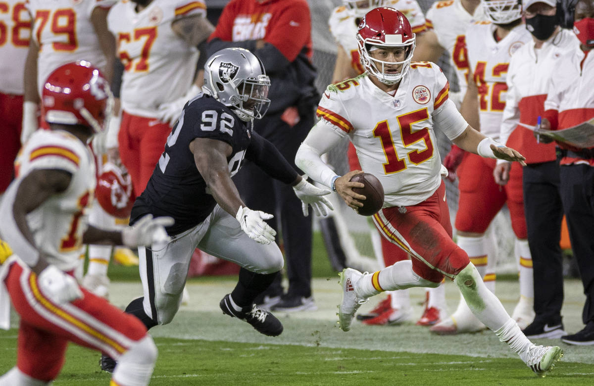 Kansas City Chiefs quarterback Patrick Mahomes (15) scrambles past Las Vegas Raiders defensive ...