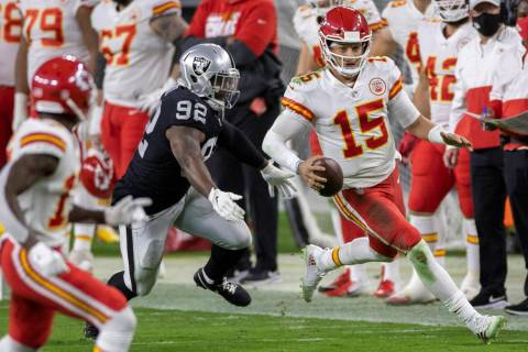 Kansas City Chiefs quarterback Patrick Mahomes (15) scrambles past Las Vegas Raiders defensive ...