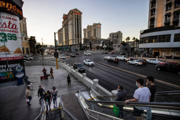 People take an escalator to a pedestrian bridge over Flamingo Road at the Las Vegas Strip Thurs ...