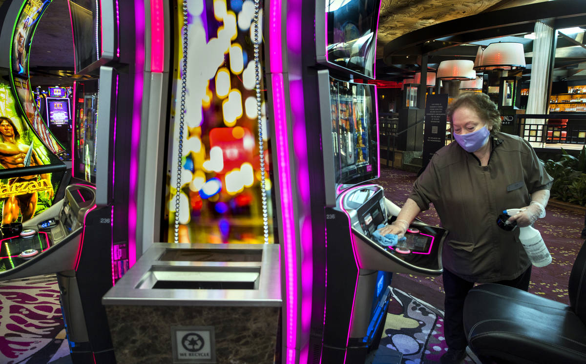 Gloria Acuna sanitizes another slot machine as guests arrive as the Mirage reopens following a ...