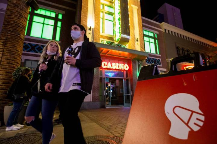 Some visitors to The LINQ Promenade wore masks while others didn't as signs asked them to on Su ...