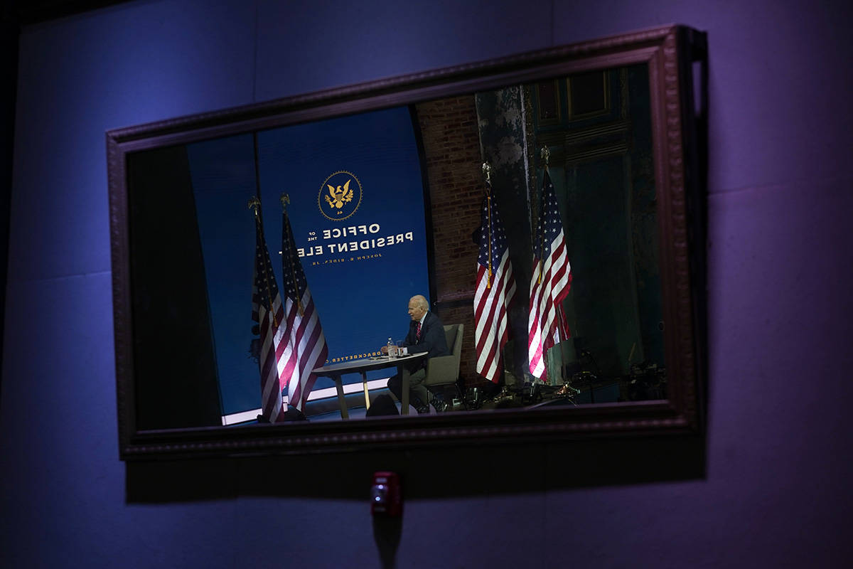 President-elect Joe Biden is reflected in a mirror as he meets virtually with the United States ...