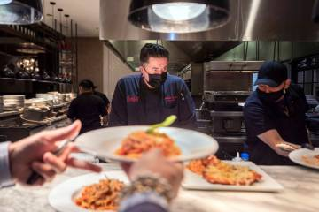 Executive sous chef Christian Gonzalez, center, oversees dishes going out to be served at Buddy ...