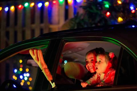 Jayleen Valenzuela, 7, left, and Adonai Valenzuela, 2, right, marvel at the holiday decorations ...