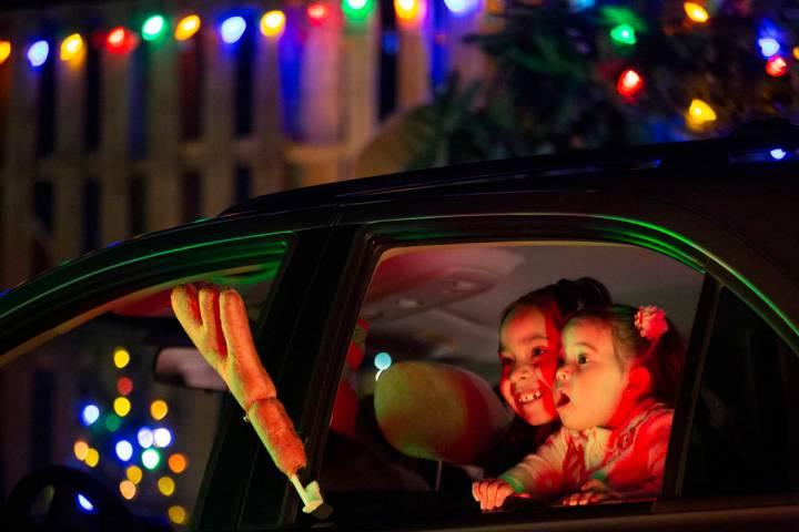 Jayleen Valenzuela, 7, left, and Adonai Valenzuela, 2, right, marvel at the holiday decorations ...