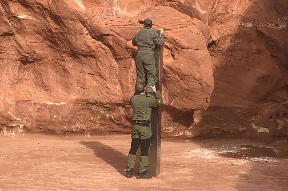 Two crew members show the height of a monolith discovered Nov. 18, 2020, in a remote southeast ...