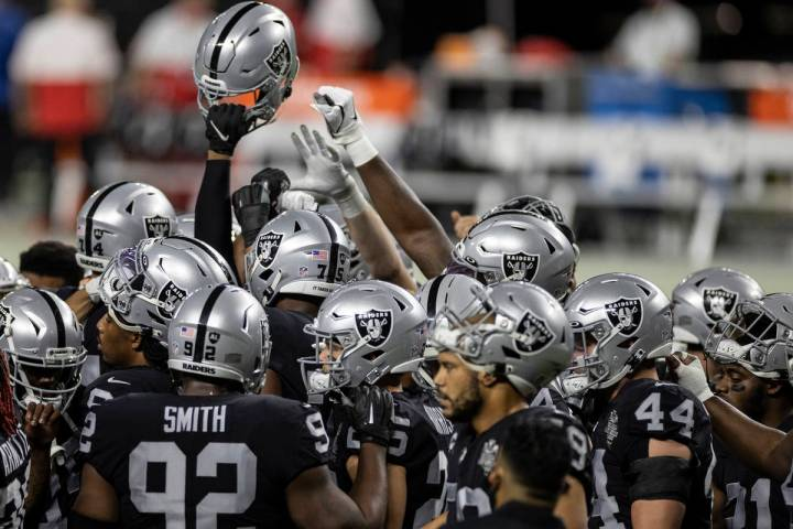 The Las Vegas Raiders warm up before the start of an NFL football game against the Kansas City ...