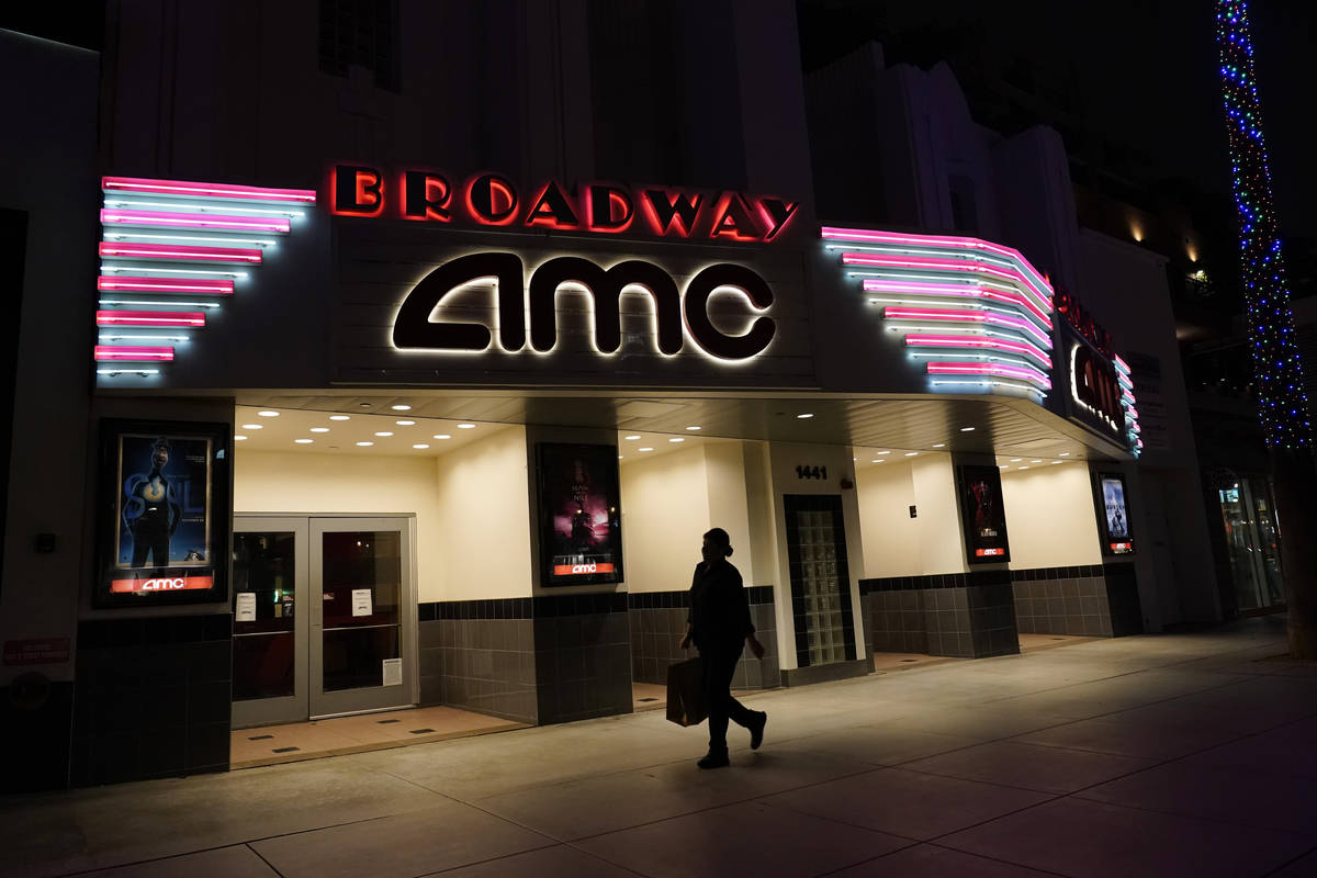 In this Thursday, Nov. 19, 2020, file photo, a shopper walks past a closed AMC movie theater in ...