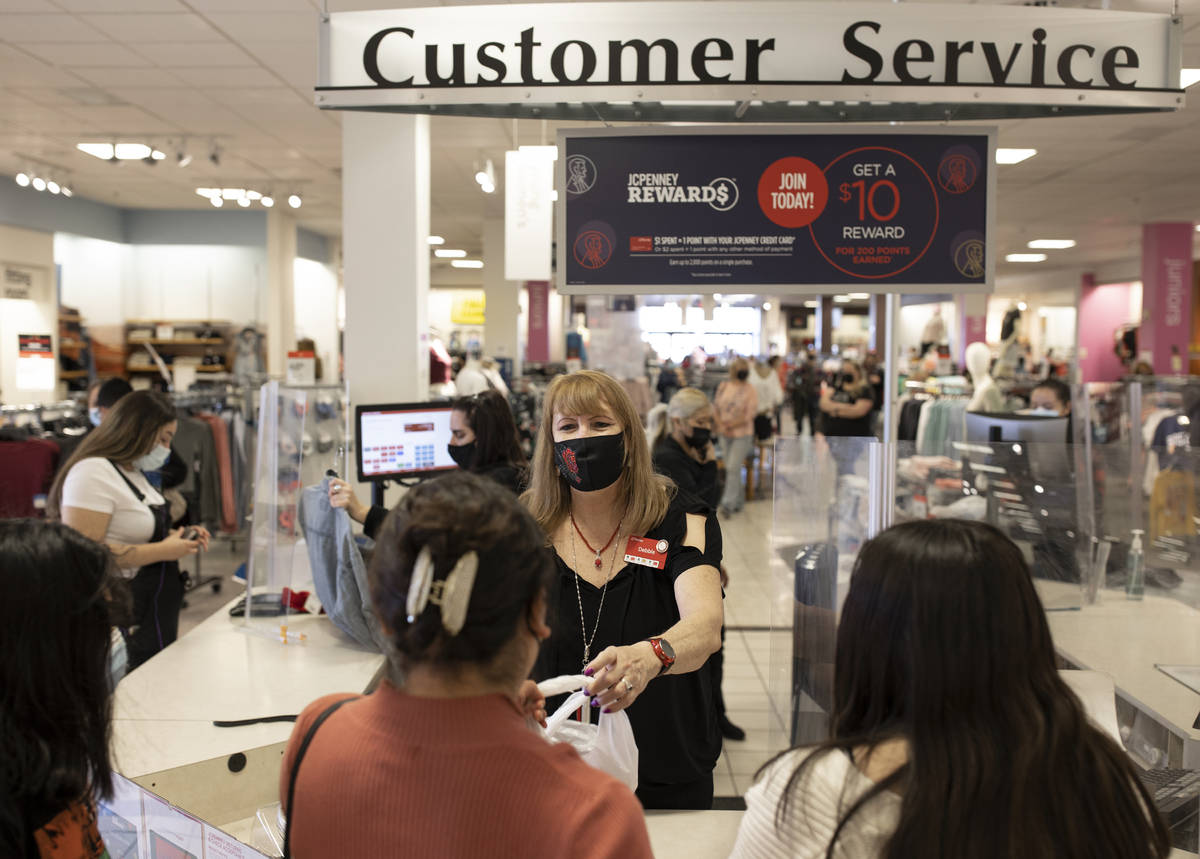 J.C. Penney cashier Debbie Steinberg, middle, checks out customers during Black Friday at the s ...