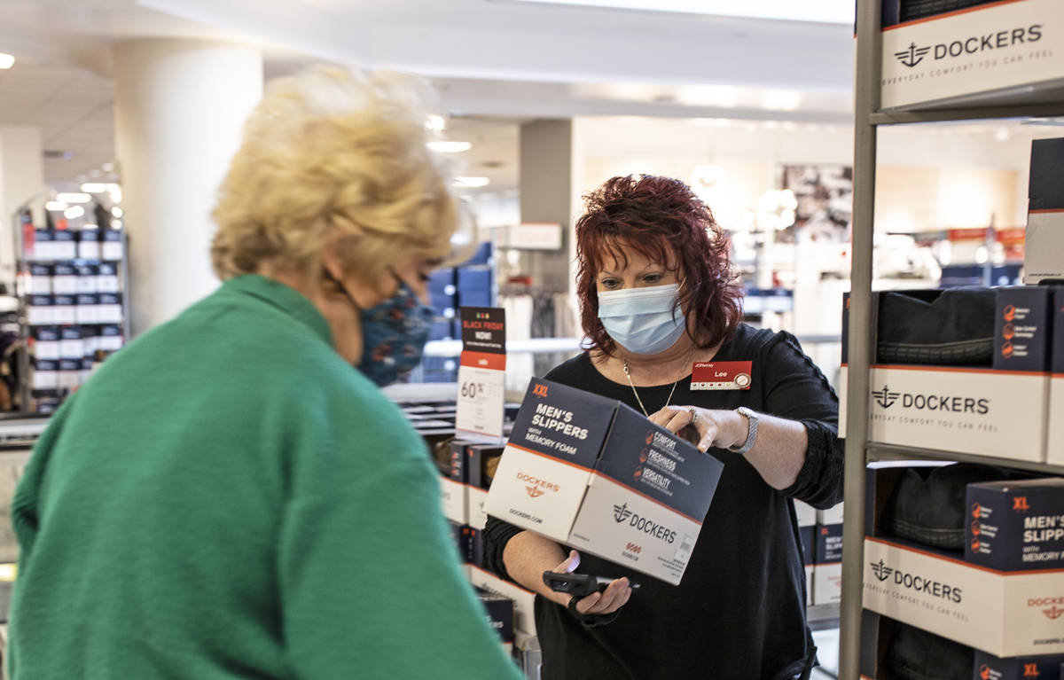 J. C. Penney general manager Lee Beamon, right, helps a shopper during Black Friday at the stor ...