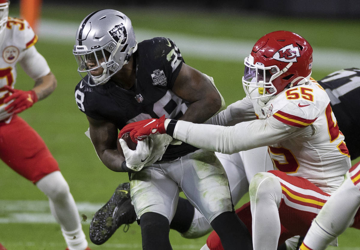 Las Vegas Raiders running back Josh Jacobs (28) fights for extra yardage against Kansas City Ch ...