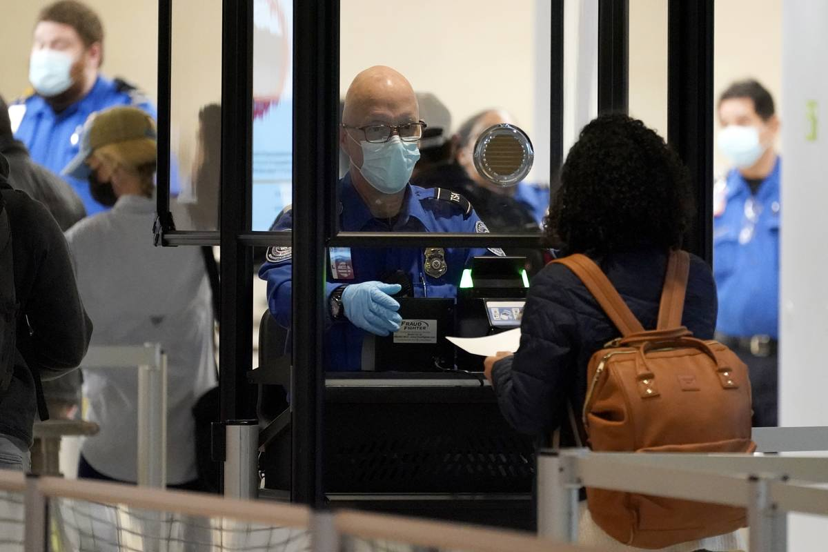 A TSA agent assist a travel at a security checkpoint at Love Field Airport in Dallas, Tuesday, ...