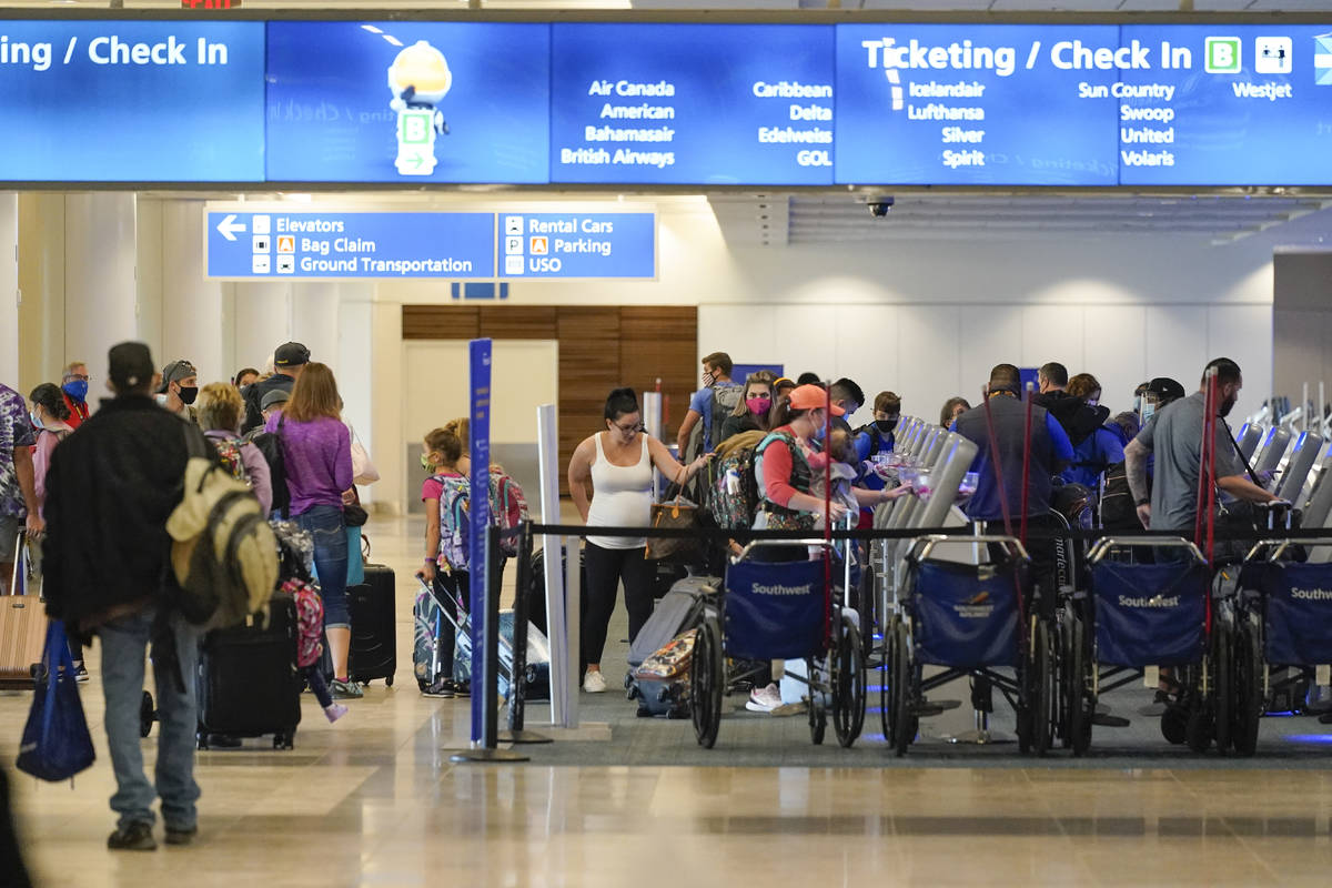 Holiday travelers check in at kiosks near an airline counter at Orlando International Airport T ...