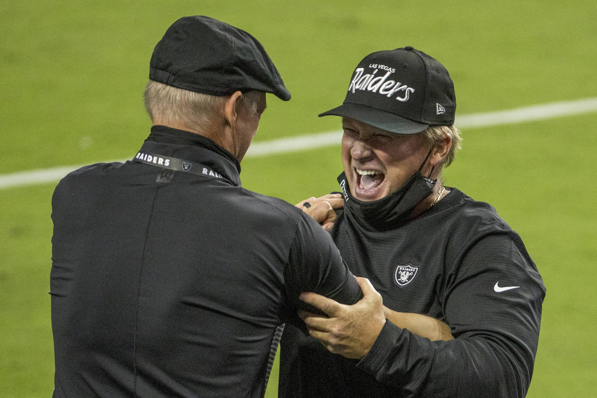 Las Vegas Raiders general Manager Mike Mayock, left, celebrates a win with head coach Jon Grude ...