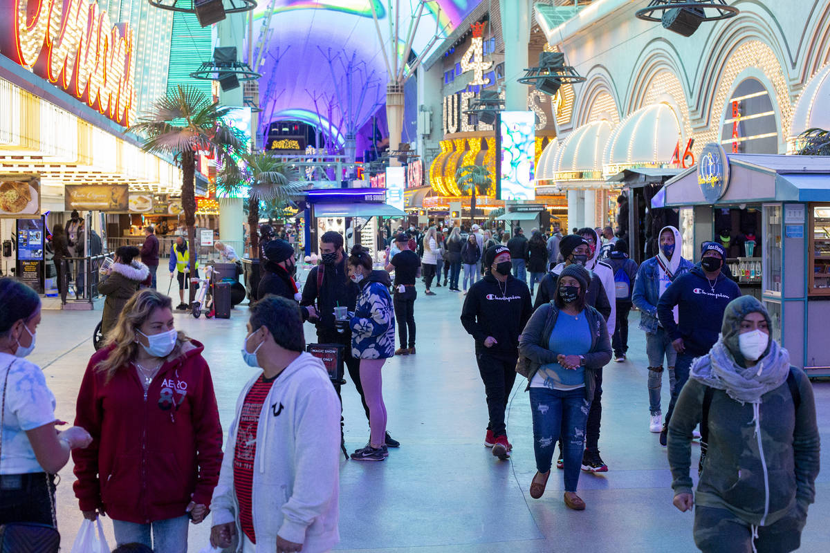 Visitors to Fremont Street Experience dress for cool temperatures on Thursday, Nov. 26, 2020, i ...
