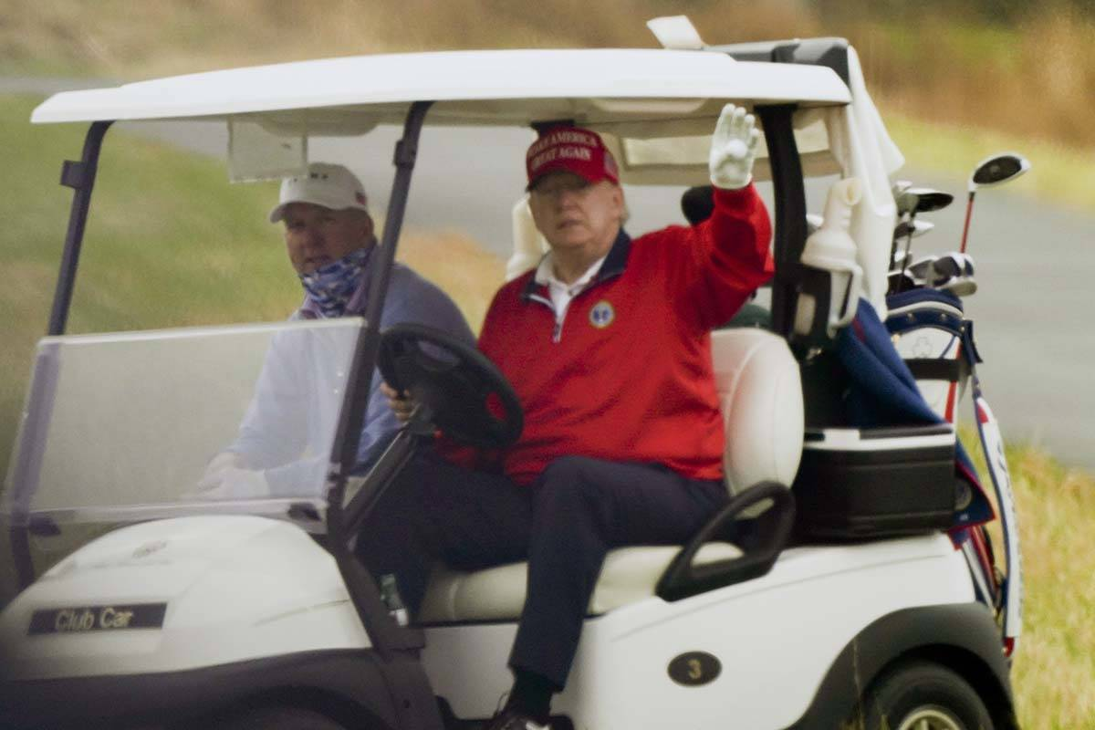 President Donald Trump waves from a golf cart as he plays golf at Trump National Golf Club, Fri ...