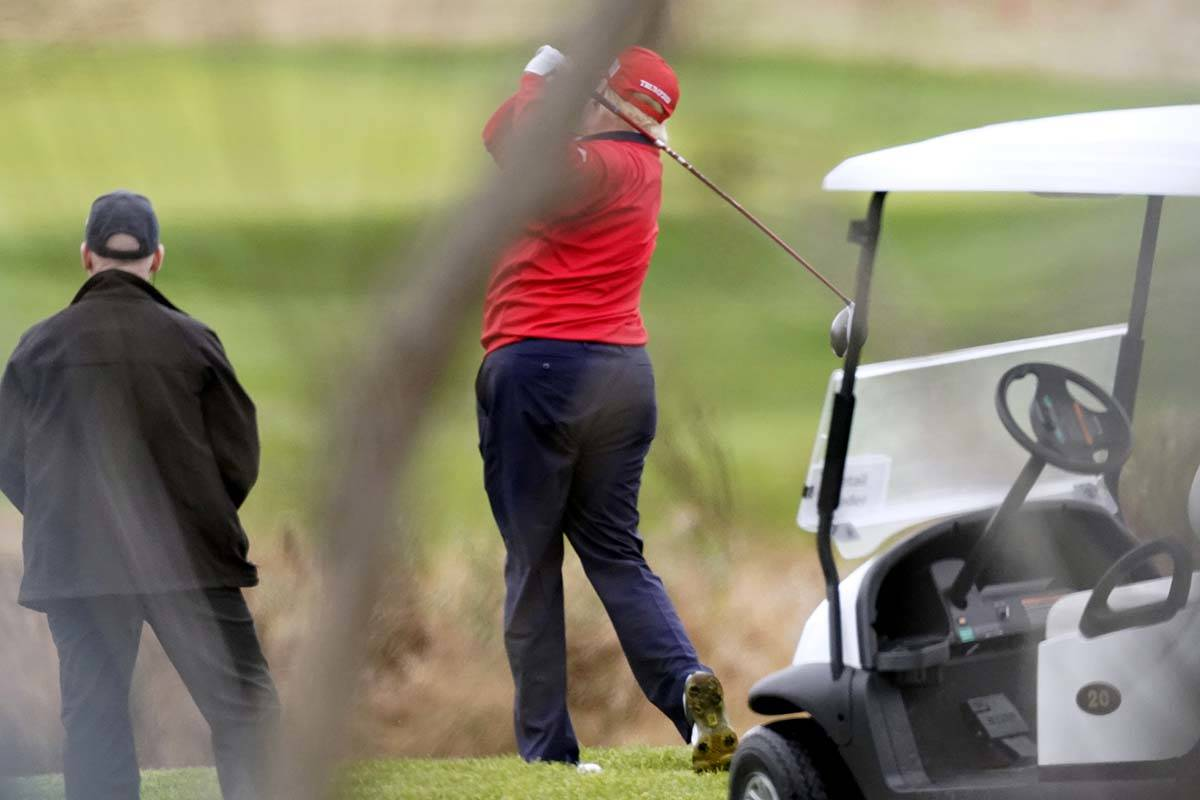 President Donald Trump takes a practice swing as he plays golf at Trump National Golf Club, Fri ...