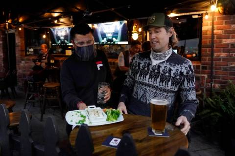 A waiter serves food to a customer at Ye Olde King's Head on Thursday, Nov. 19, 2020, in Santa ...