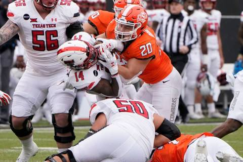 Texas Tech running back Xavier White (14) is tackled by Oklahoma State linebacker Malcolm Rodri ...