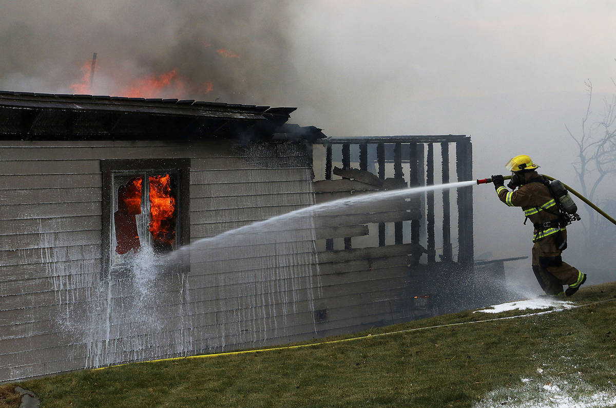 A firefighter tries to save a home during the Pinehaven Fire in the Caughlin Ranch area of Reno ...