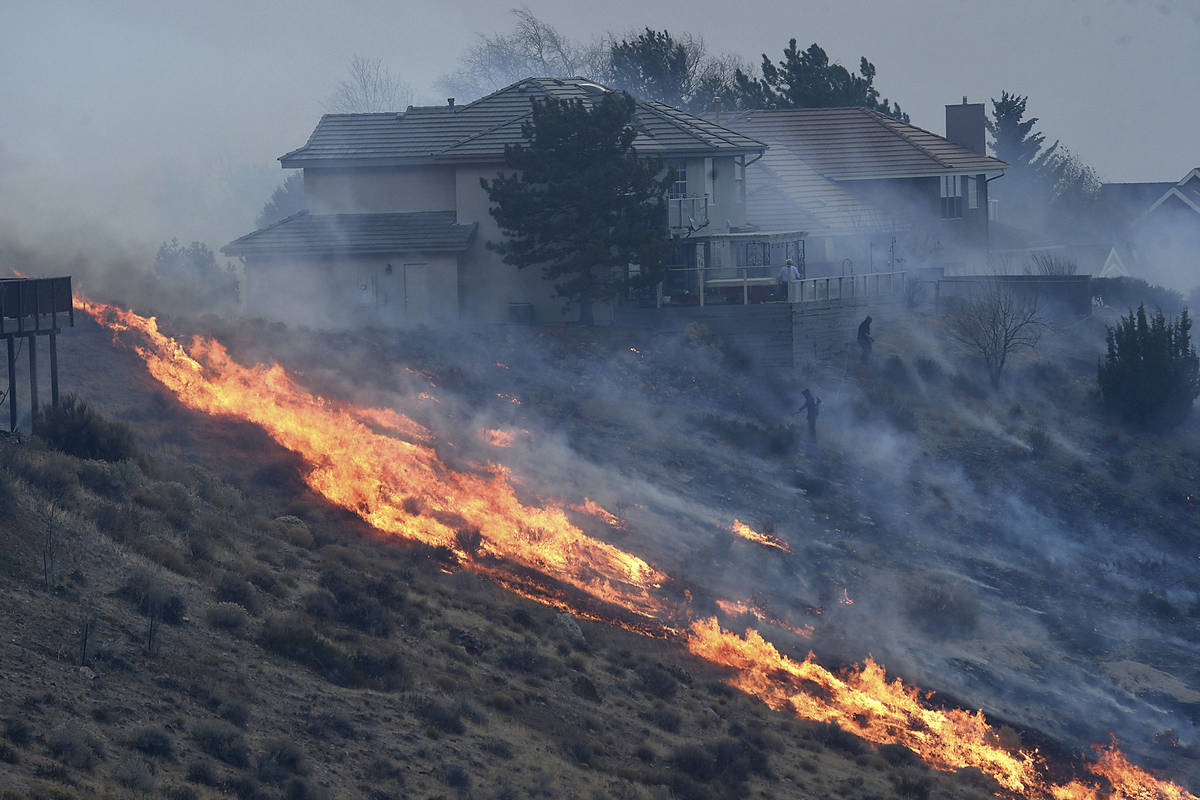 People try to protect their homes during the Pinehaven Fire in the Caughlin Ranch area of Reno ...