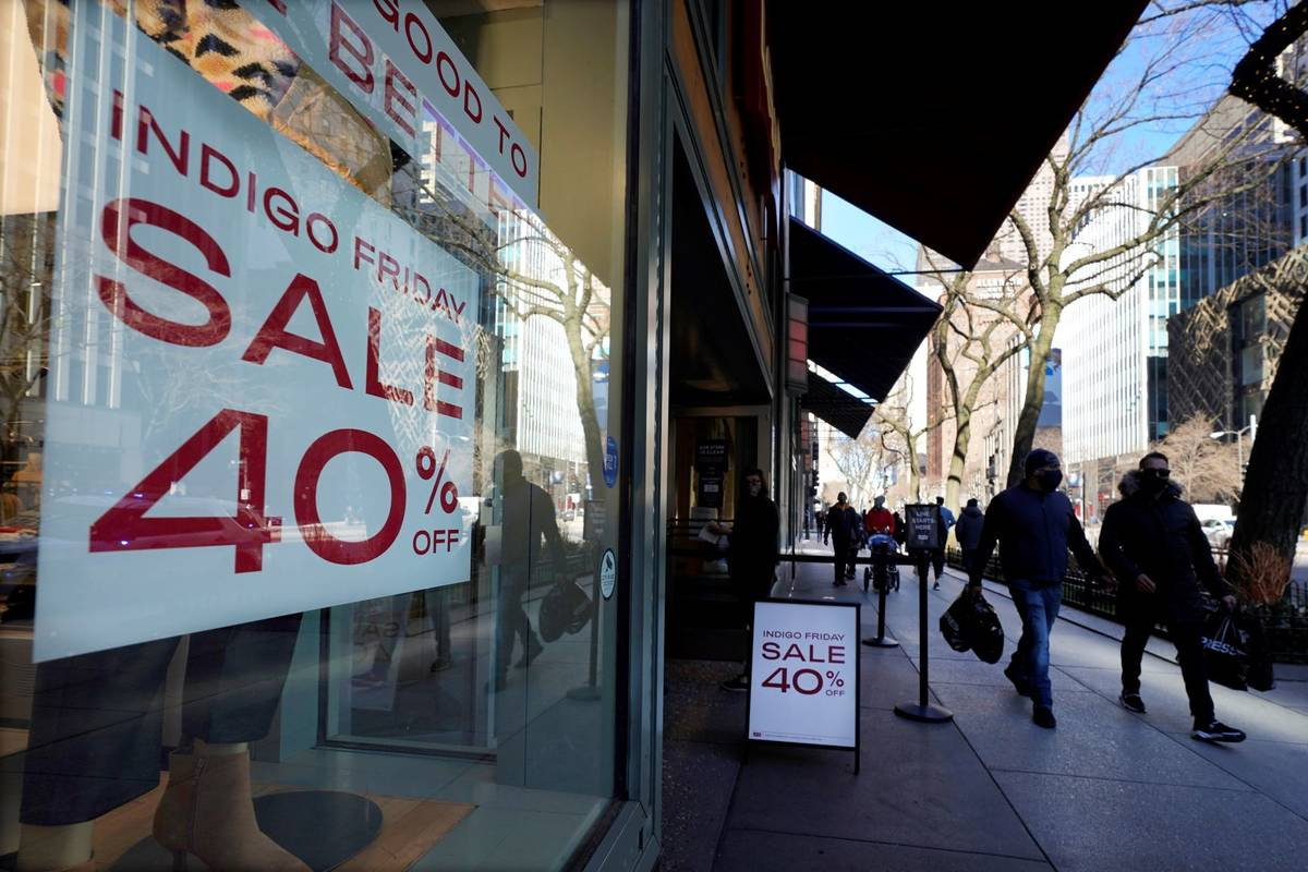 Shoppers pass an Indigo Friday 40% Off sign Saturday, Nov. 28, 2020, on Chicago's famed Magnifi ...