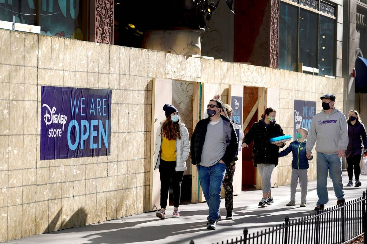 Shoppers pass Saturday, Nov. 28, 2020, an open Disney Store that is still partially boarded up ...