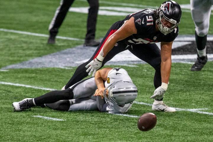 Las Vegas Raiders quarterback Derek Carr (4) remains down after being sacked as Atlanta Falcons ...