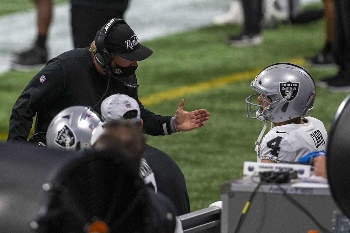 Las Vegas Raiders head coach Jon Gruden speaks to quarterback Derek Carr (4) on the sideline af ...