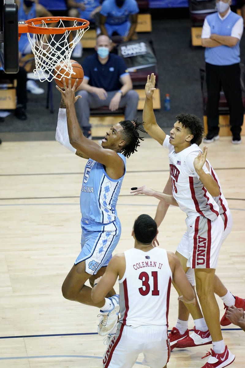 North Carolina forward Armando Bacot (5) drives the ball to the basket past UNLV forward Reece ...