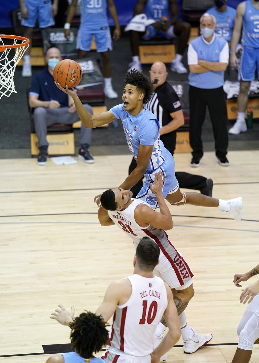 North Carolina guard Puff Johnson (14) leaps over UNLV guard Marvin Coleman (31) to shoot for t ...