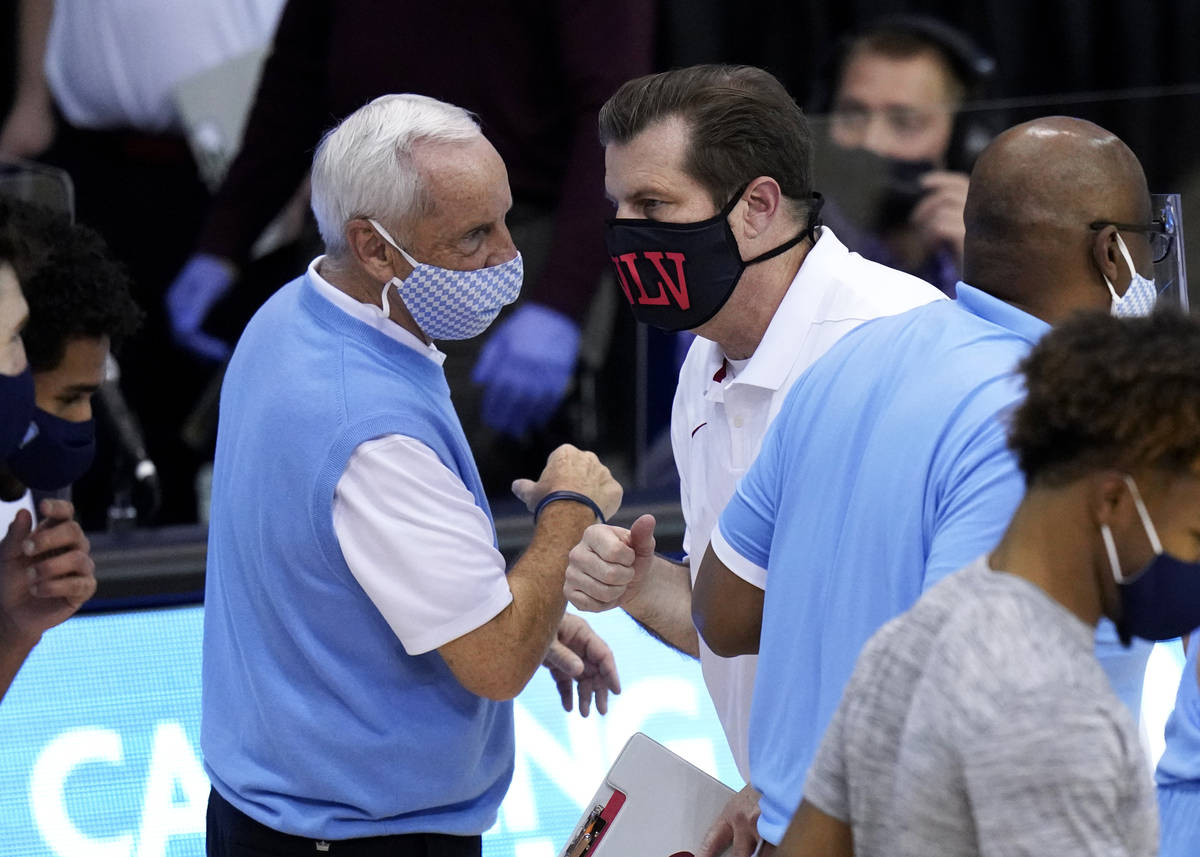 North Carolina head coach Roy Williams bumps-fists and talks with UNLV head coach T.J. Otzelber ...