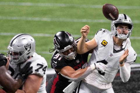 Las Vegas Raiders quarterback Derek Carr (4) is strip sacked by Atlanta Falcons defensive tackl ...