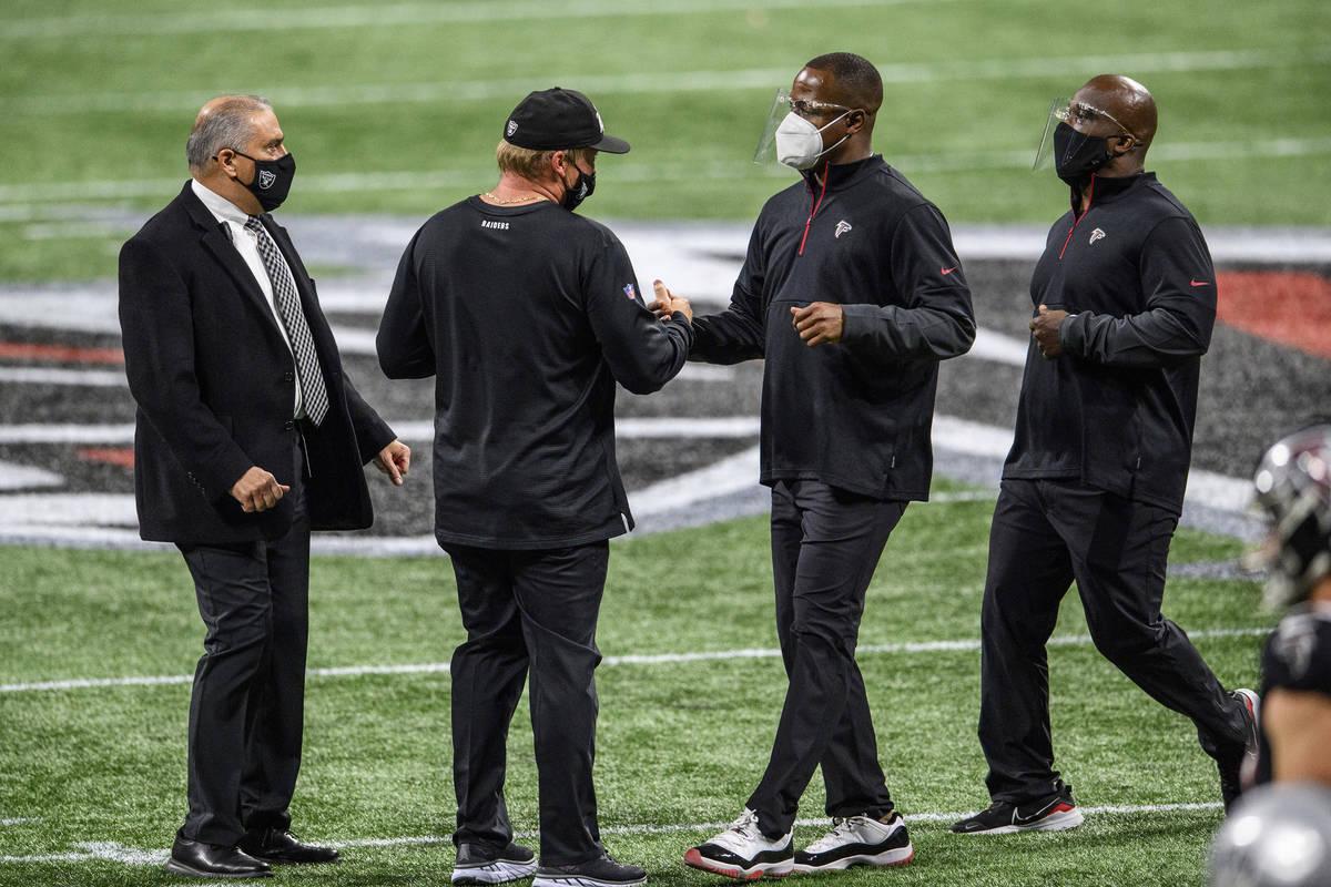 Atlanta Falcons interim head coach Raheem Morris and Las Vegas Raiders head coach Jon Gruden sh ...
