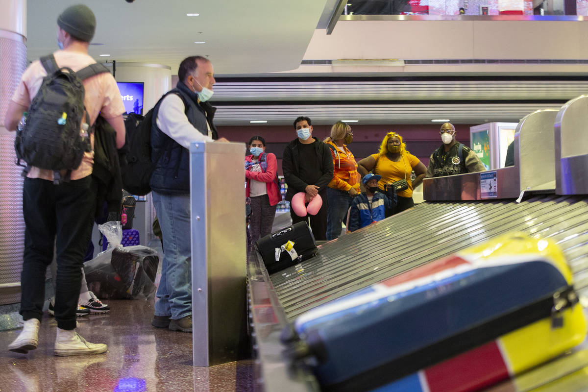 Visitors wait for their luggage ahead of the Thanksgiving holiday at McCarran International Air ...