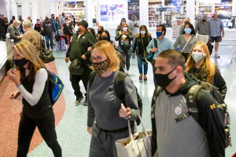 A crowd heads toward baggage claim at McCarran International Airport on Sunday, Nov. 22, 2020, ...