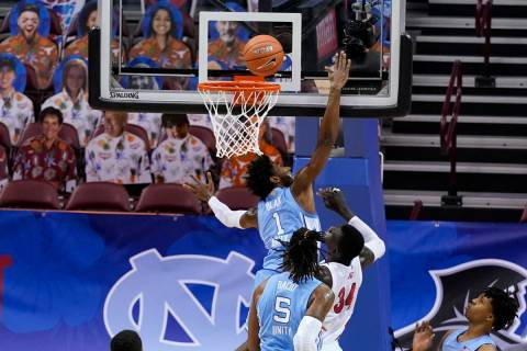 North Carolina guard Leaky Black (1) tries to block a shot by UNLV forward Cheikh Mbacke Diong ...