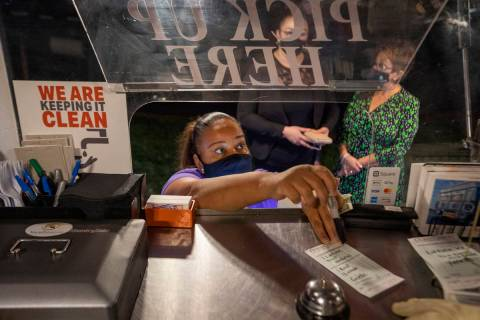 Owner Jinelle Batista places a customer's order as YourPanadas empanada truck pays a visit to A ...