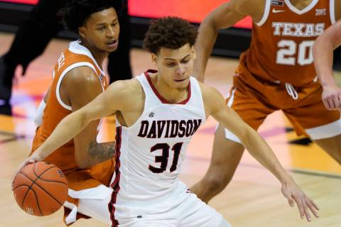 Davidson guard Kellan Grady (31) drives the ball away from Texas forwards Gerald Liddell (0) an ...