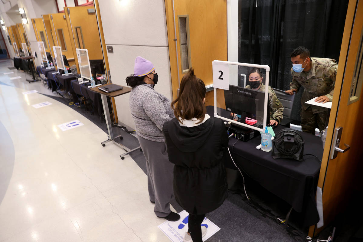 Nevada National Guard specialists Alondra Felix and Daniel Merchant check in Ana Pena, left, an ...