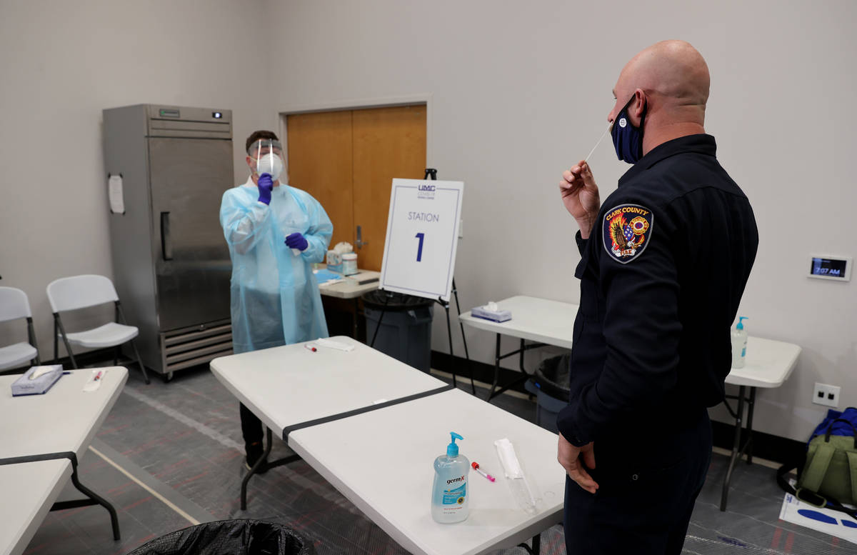 Travis Haldeman, a Clark County Fire Department engineer, uses a nasal swab for a COVID-19 test ...