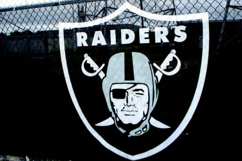 The Raiders logo hangs over a fence surrounding the Oakland Coliseum in Oakland, Calif., on Sun ...