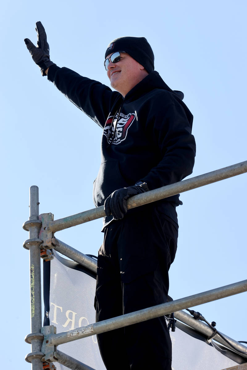 Chet Buchanan of KLUC-FM waves at passing cars atop a 30-foot scaffolding during his toy drive ...