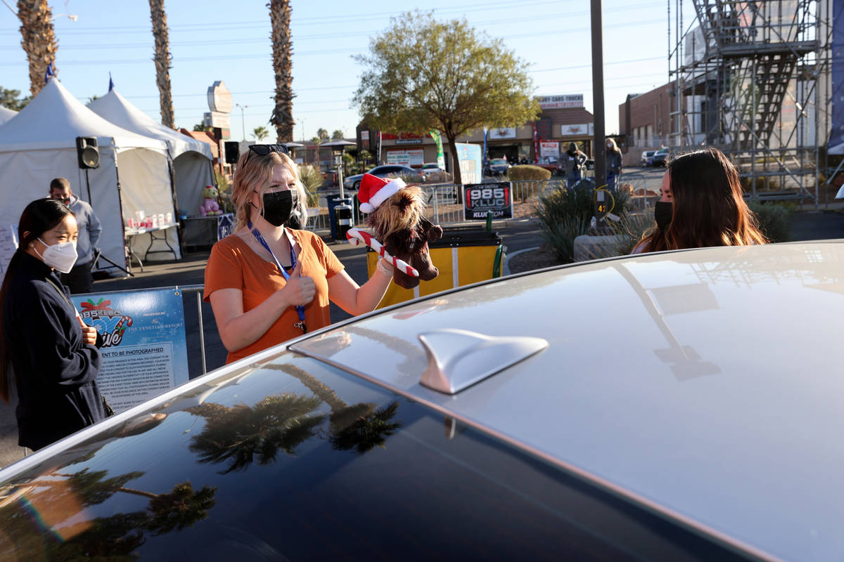 Volunteer Hanna Andersen thanks a driver who donated toys during the Chet Buchanan KLUC-FM toy ...