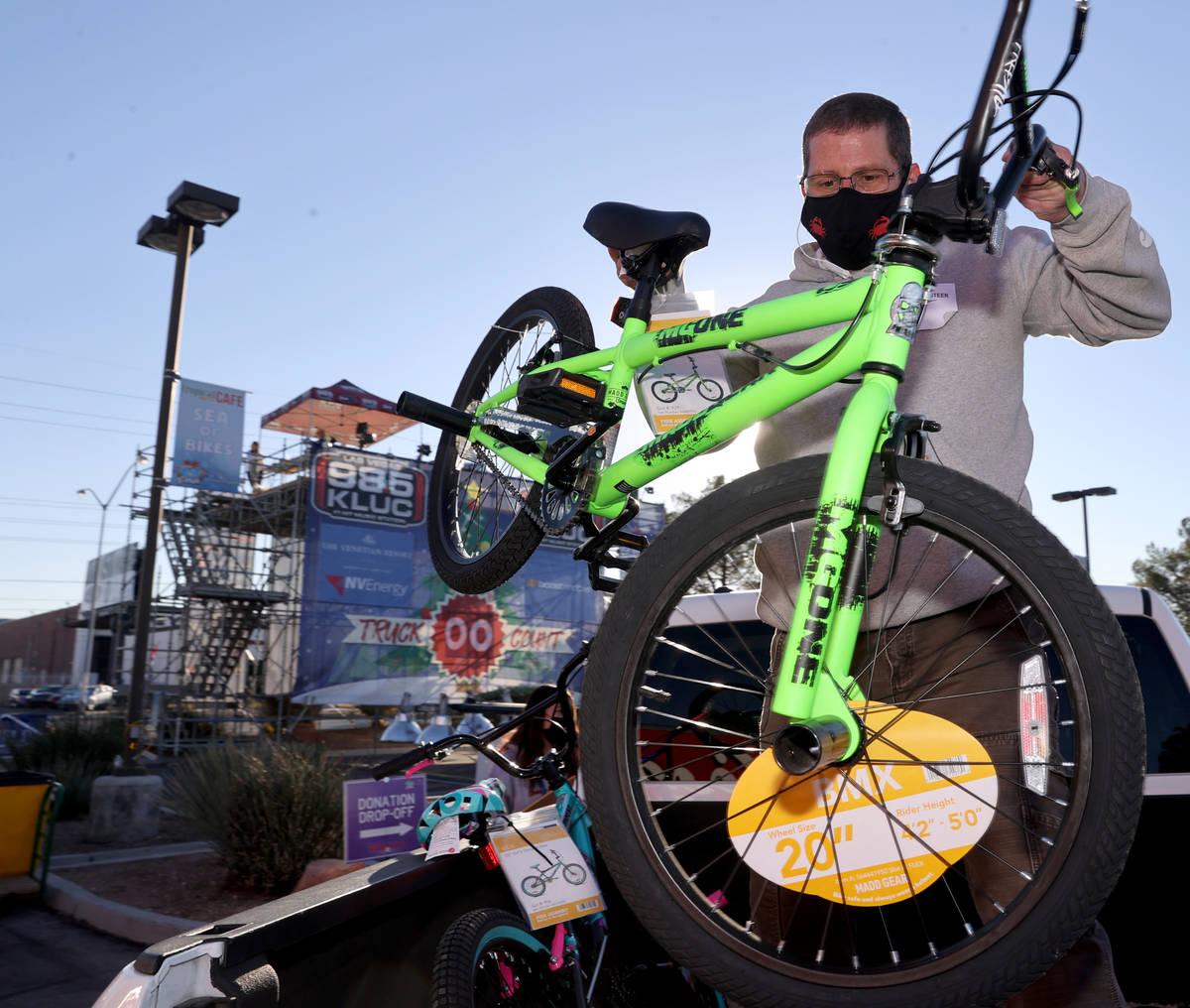 Volunteer Matt Rose loads a donated bike during the Chet Buchanan KLUC-FM toy drive in the NV E ...