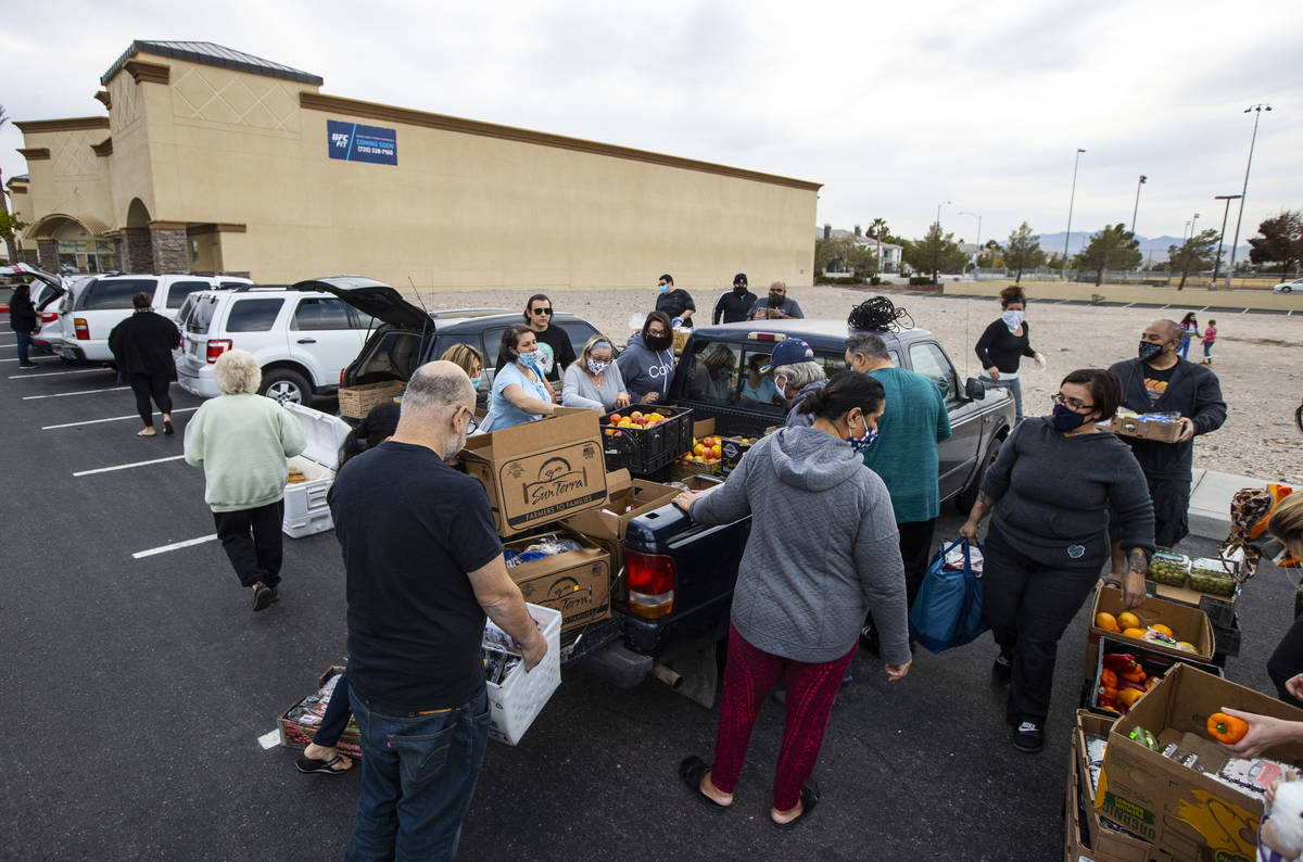 People in need get donated food from Amber Stevenson, upper right, wearing a bandana, at a shop ...