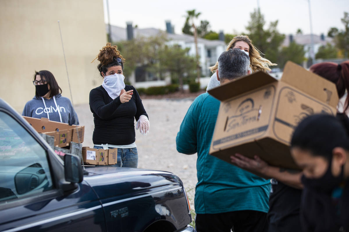 Amber Stevenson, left, gives out food to people in need at a shopping center in Las Vegas on We ...